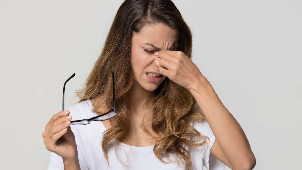 A girl taking off glasses rubbing irritated eyes
