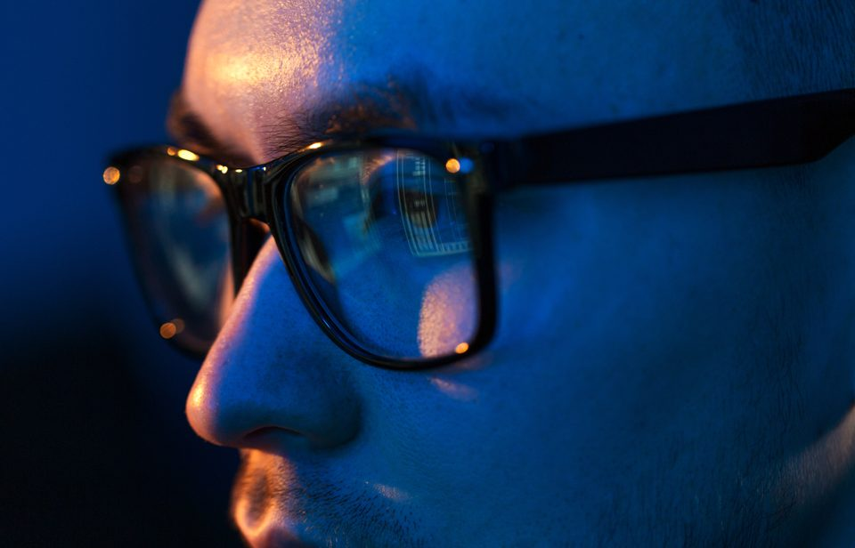 Man/woman working at computer with blue light glasses.