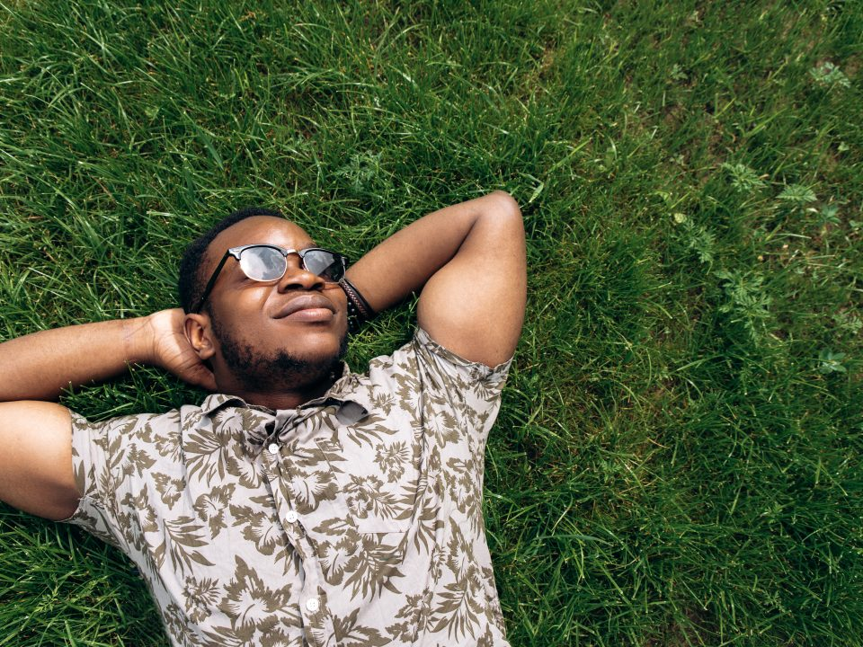 Portrait of a handsome young african american guy who is resting on grass during a warm summer day. Top view.